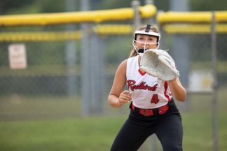 A softball player holds up her glove.