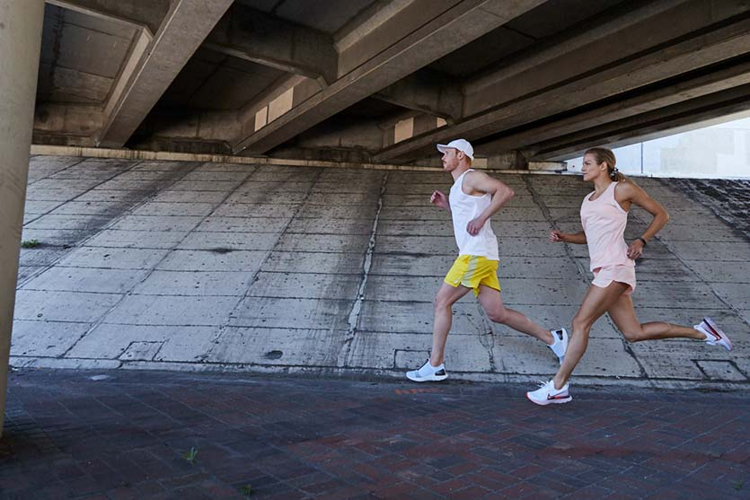 man and woman running in shorts and tanks in the summer wearing Nike running shoes