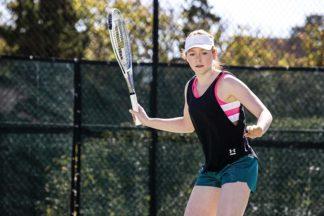 A girl holds a tennis racquet on a court.