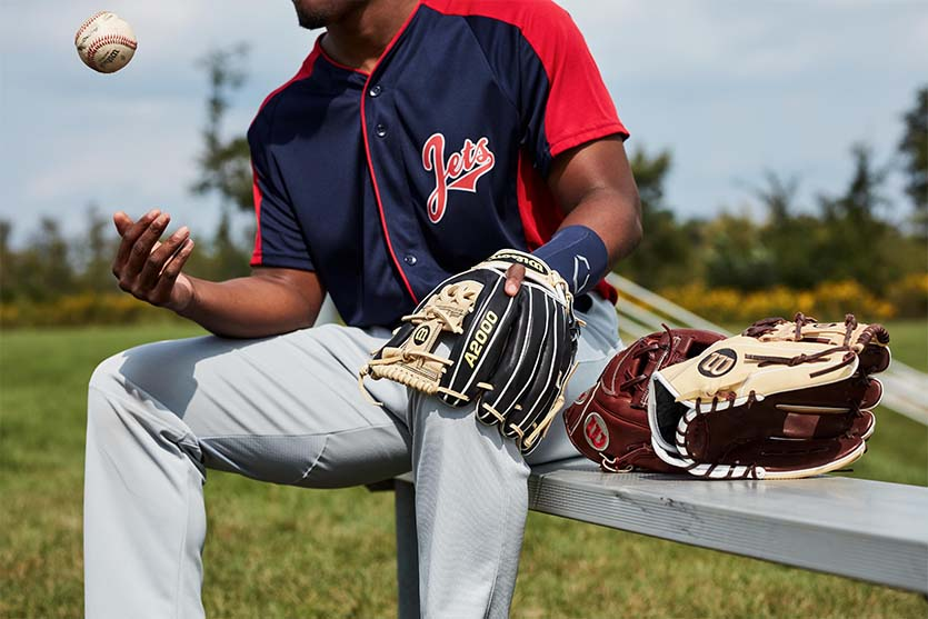 A baseball player sits on a bench next to a variety of gloves
