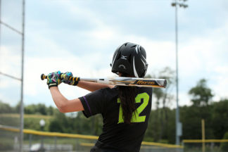 A softball player waits at bat