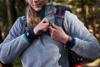 A woman prepares for a hike by clipping her backpack.
