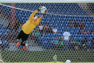 A soccer goalie makes a diving save