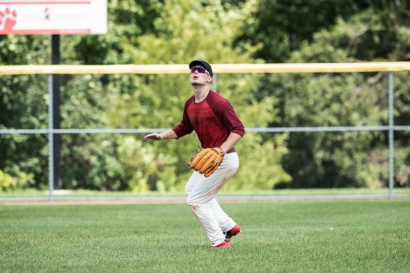 A baseball player awaits a fly ball in the outfield.
