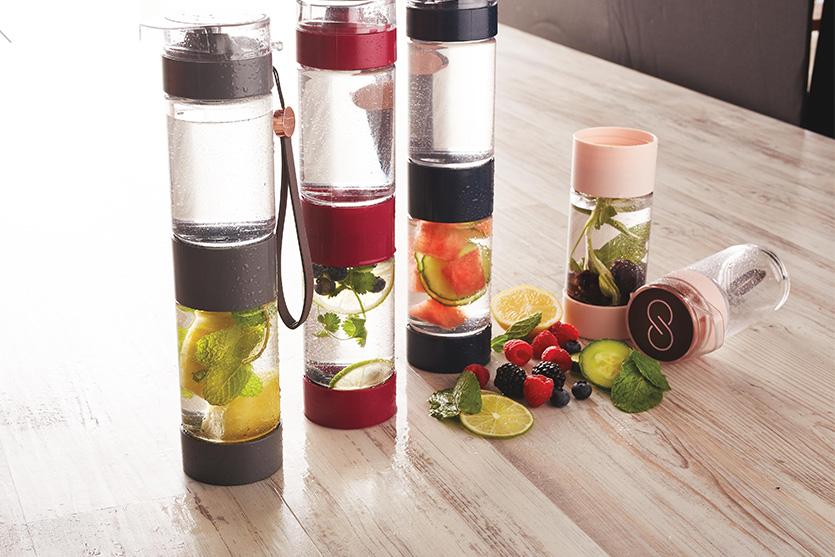 Infuser bottles with various fruits are placed on a wooden table