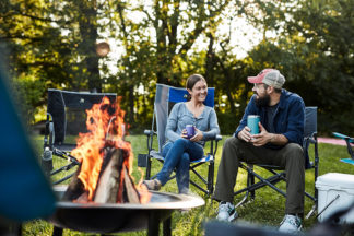 man and woman sitting around a campfire in GCI camp chairs