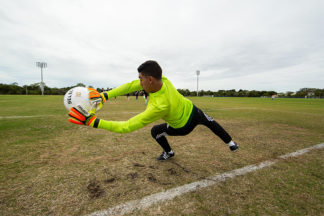 soccer goalkeeper makes save with gloves