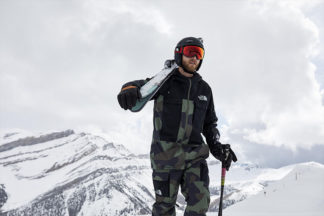 man on mountain peak wearing the north face with skis, ski helmet and ski goggles
