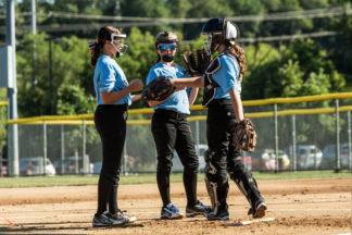 Three softball players communicate on the field