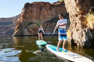 man and woman hold a sup paddle on a standup paddleboard