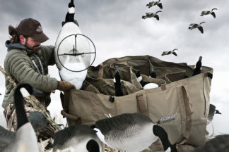 man in camo setting up waterfowl decoys for a hunt