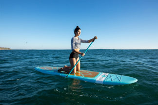 woman practices standing on sup