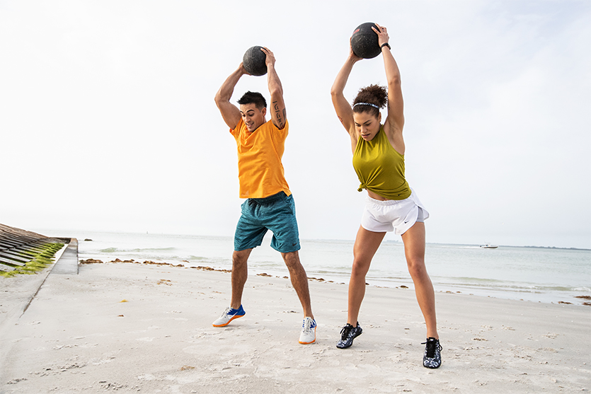 two people doing slam ball exercises at the beach wearing high-intensity shoes