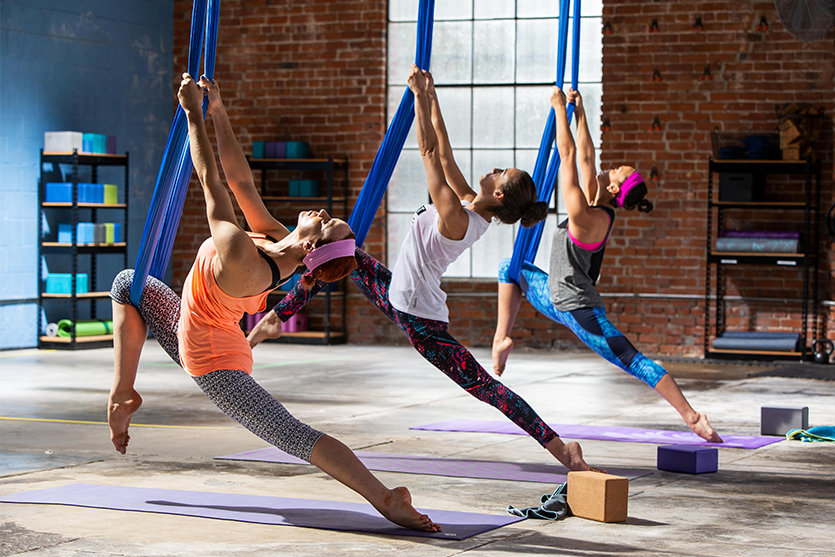 three women practice aerial yoga