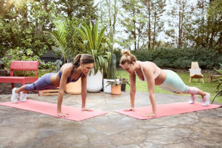 Two women perform planks outdoors.