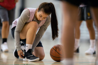 girl tying LEBRON SOLDIER XII shoe on a basketball court