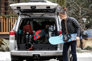 Man loads snowboarding equipment into trunk of his van.