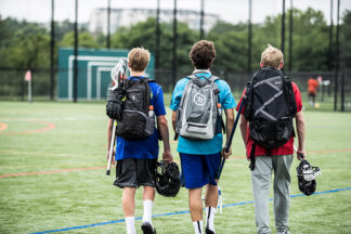 Three lacrosse players walk with their bags