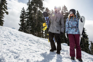 Man and woman stand with snowboarding gear on snowy mountain