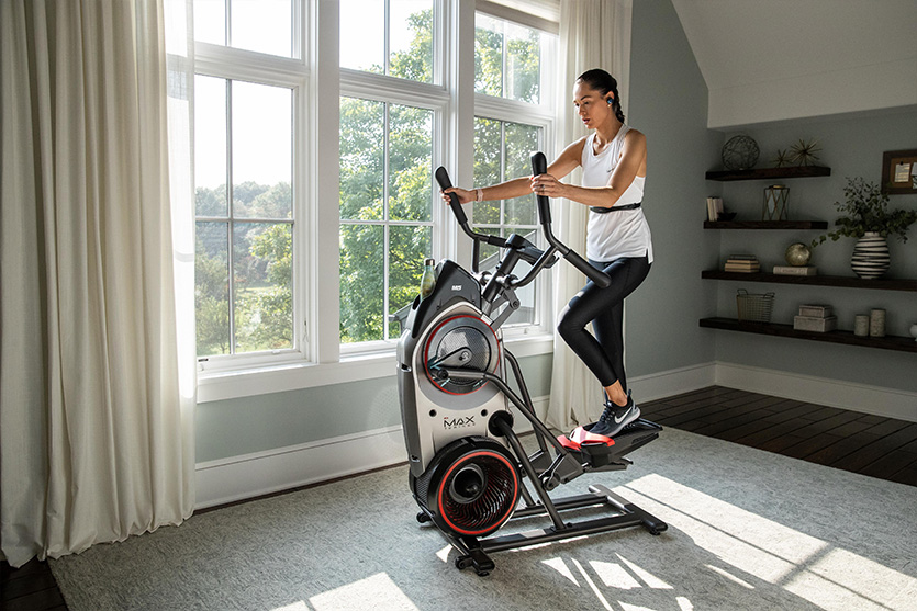 Woman uses elliptical in home