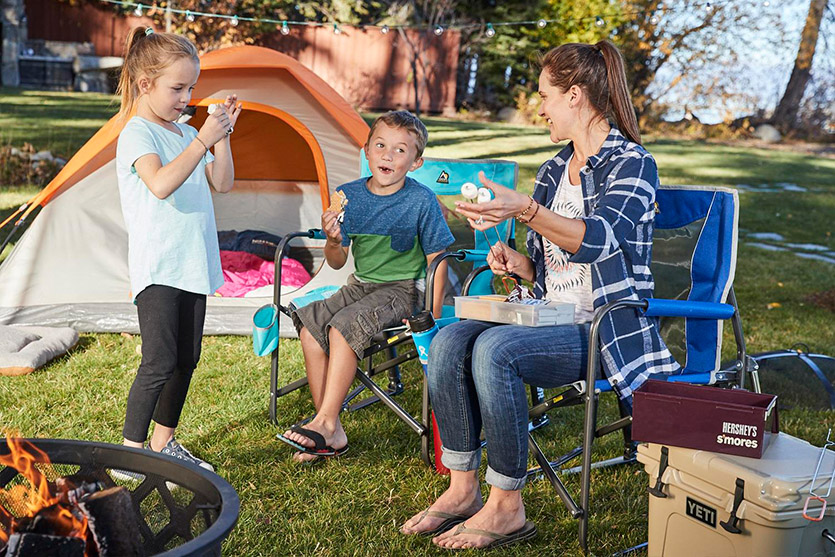 A family camps in their backyard with s'mores.