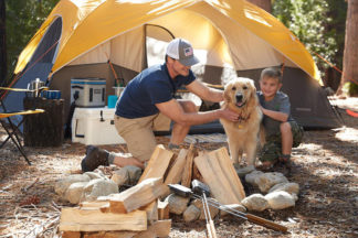 A father and son play with their dog on a campsite.