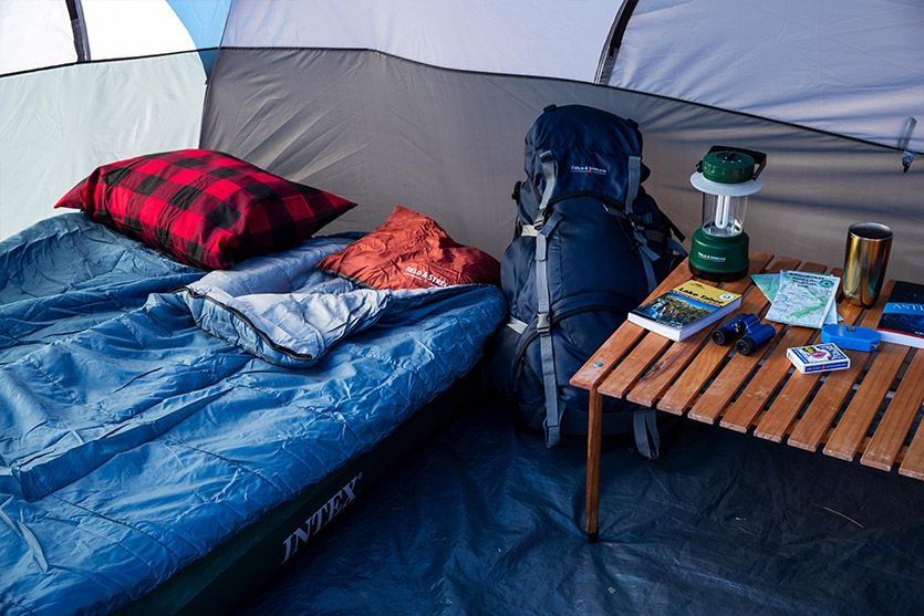 An inside of a tent featuring sleeping bags and a small table