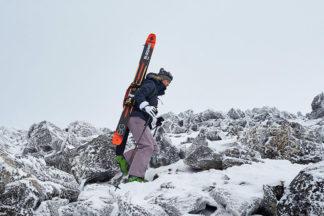 A woman climbs a snowy terrain.