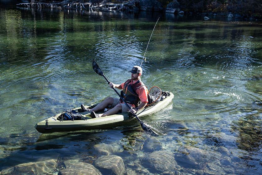 A man sits in a fishing kayak.