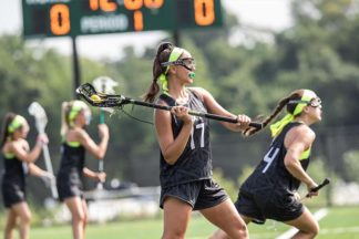 A lacrosse player practices passing the ball.