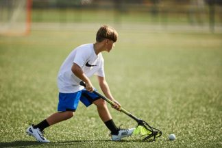 A boy playing lacrosse plays a ground ball.