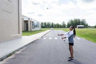 A girl practices lacrosse with wall ball drills.