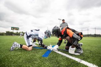 Two lacrosse players compete in a faceoff.