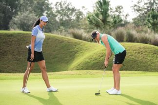 Two women on a golf course.