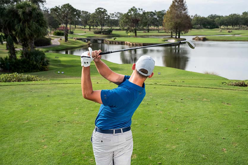 A man on a golf course swings near water.
