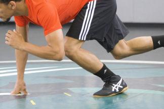 A wrestler demonstrates a downblock.