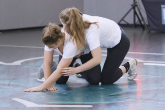 Two wrestlers demonstrate a granby roll.