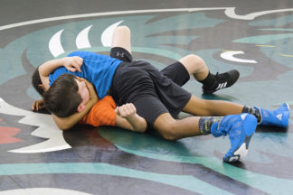 One wrestler pins another.