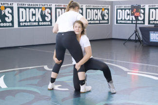 One wrestler performs a double leg takedown of another wrestler.