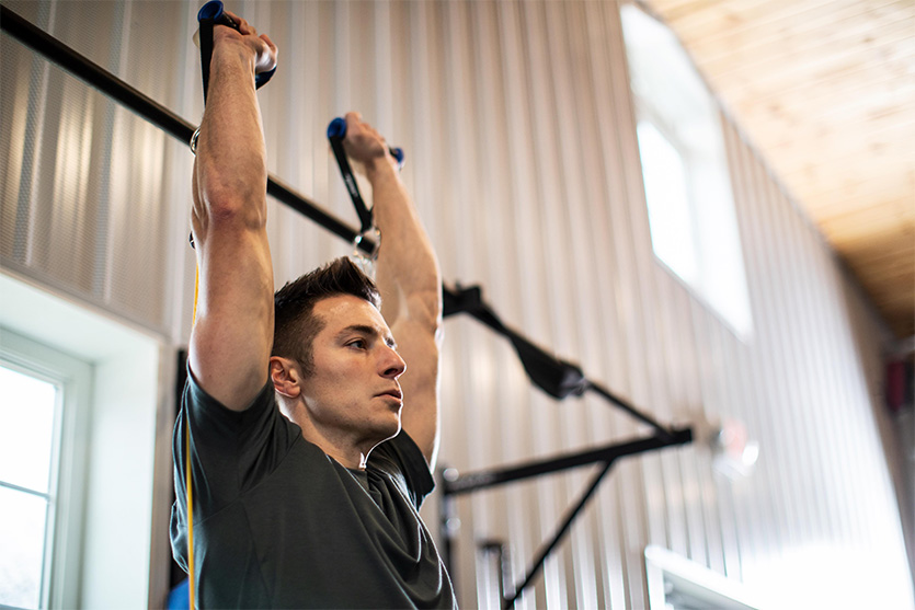 man in gym doing resistance band exerices