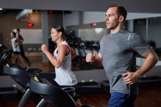 man and woman running on treadmills at the gym
