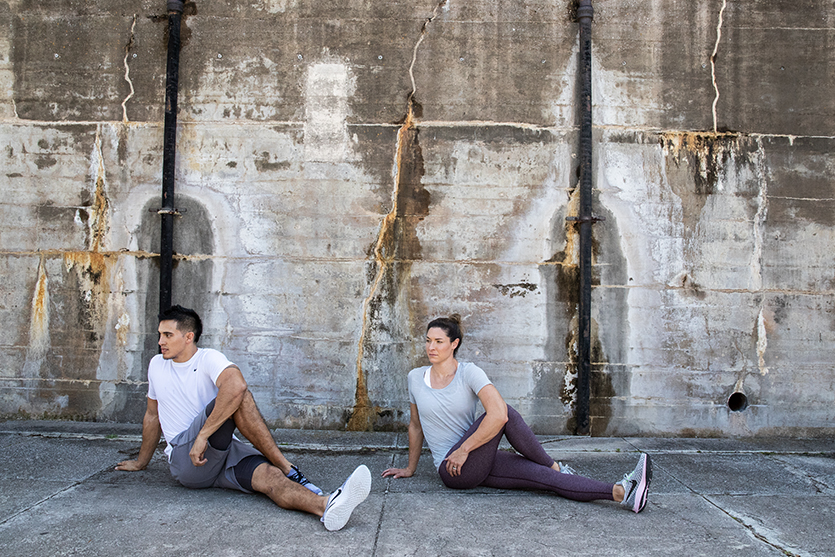 man and woman doing post-run stretches