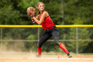 softball player exchanging a throw in a game