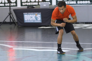A wrestler performs the stance and motion drill.