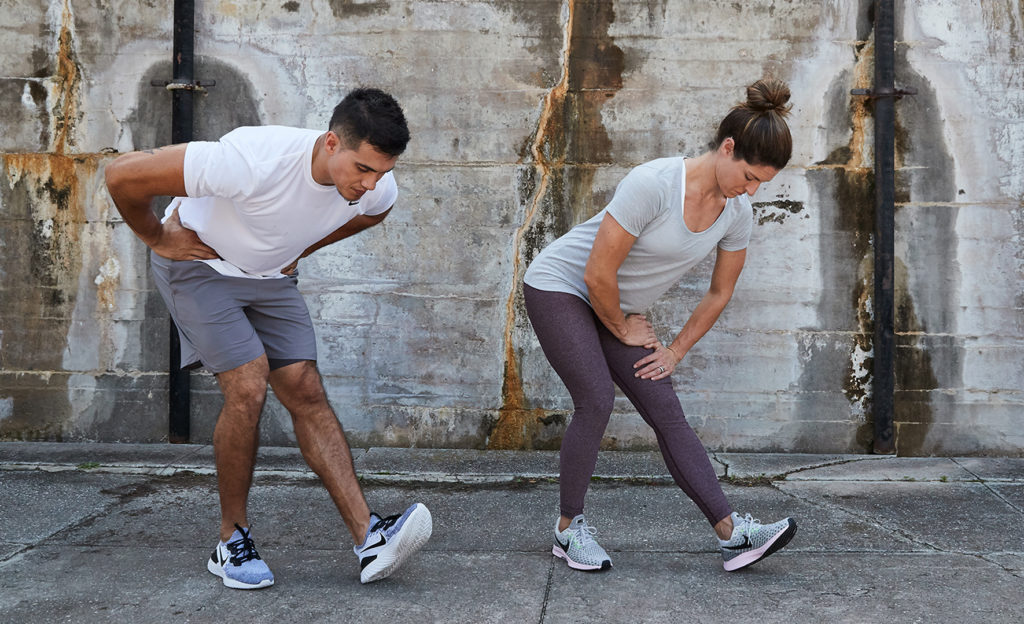 man and woman doing standing hamstring stetches