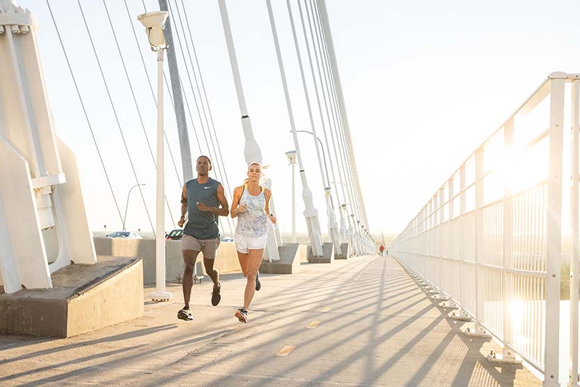 A male and female running on a bridge