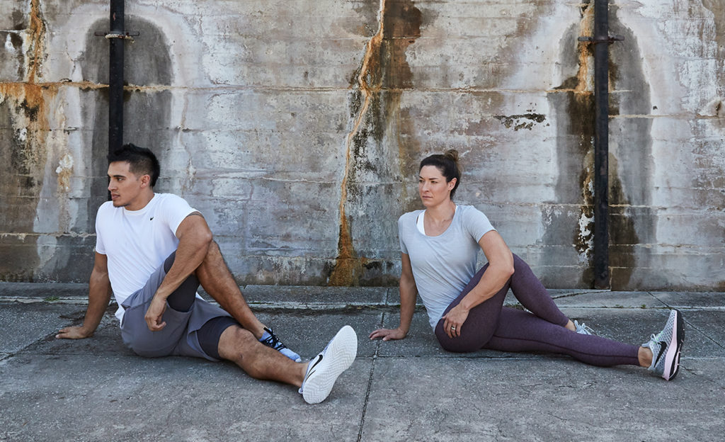 man and woman doing twisted glute stretches