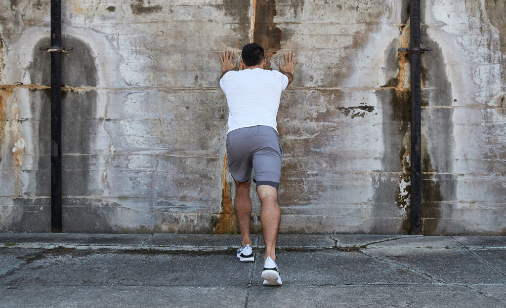 man doing calk stretches against a wall