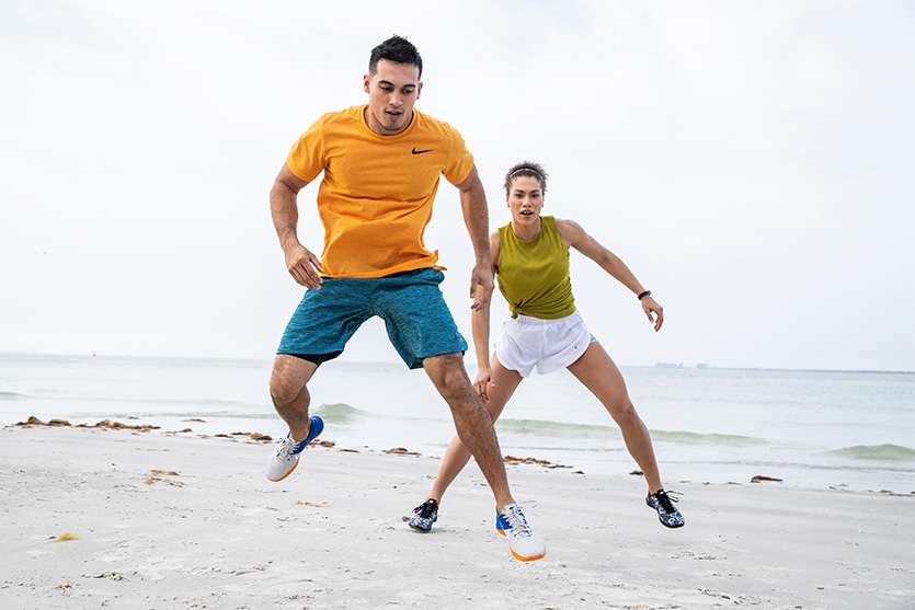 man and woman working out on the beach
