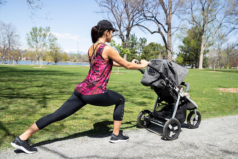 mom doing lunges with a jogging stroller in a park